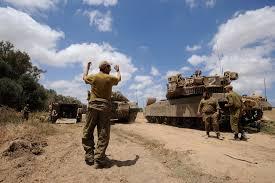 An Israeli soldier directing a Merkava tank, at an army deployment area. www.jta.org