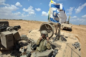 An Israeli soldier sits in an armoured personnel carrier flying the Israeli flag.
